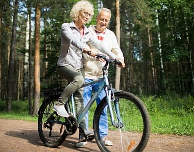 Aged blonde woman riding bicycle in the forest while her husband teaching her